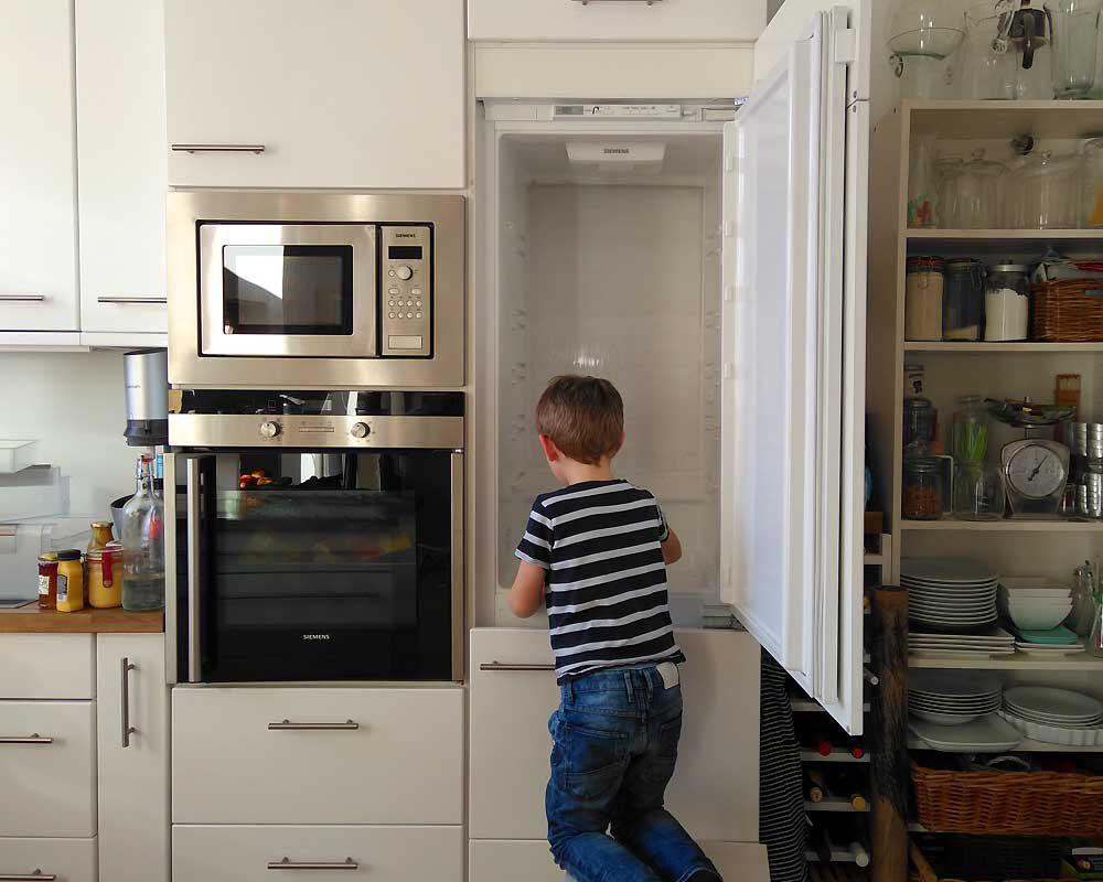 Junge hilft beim Kühlschrank säubern